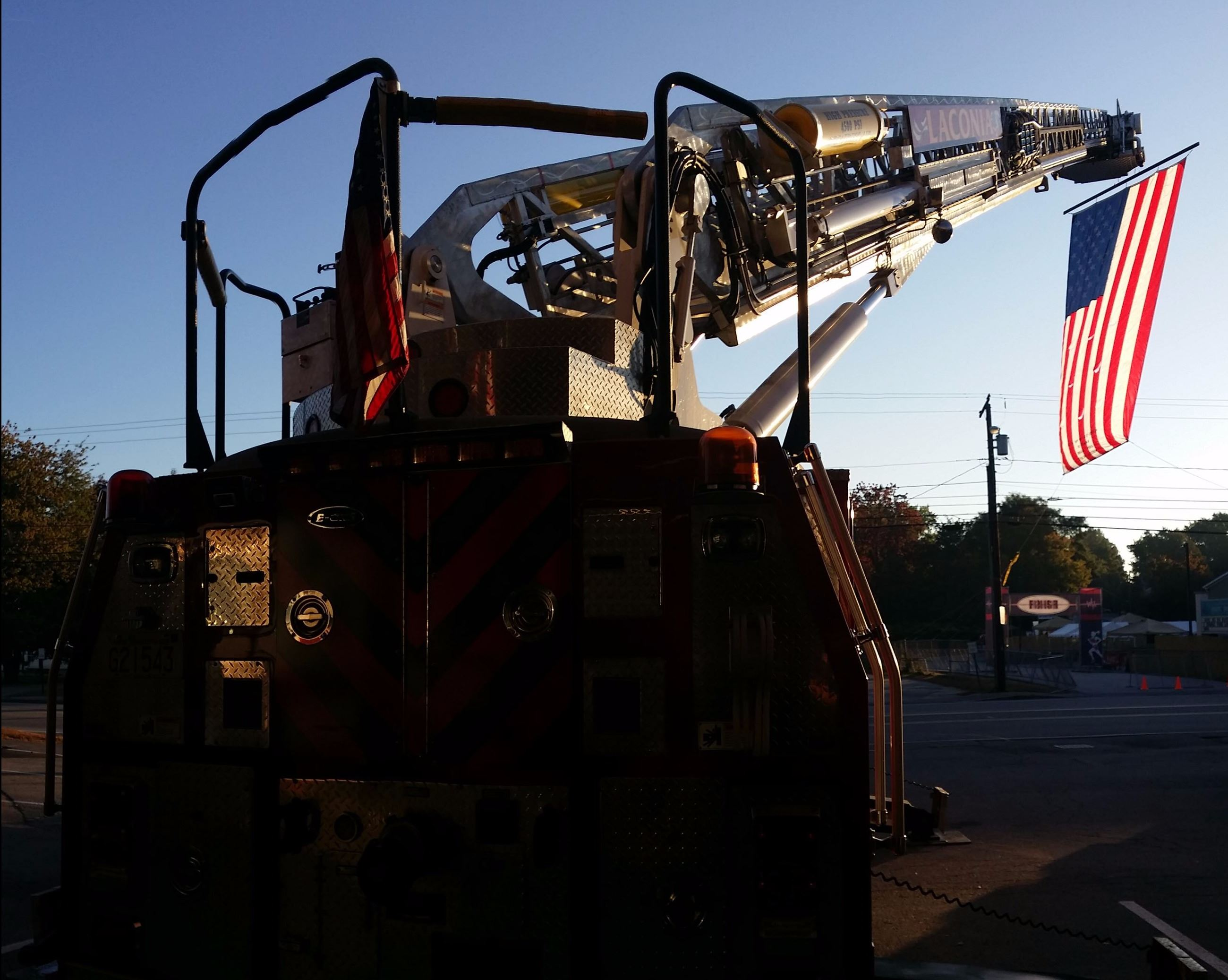 Aerial Ladder with large American flag hanging from the bucket in the morning sunlight
