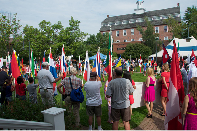 Multicultural Festival flag holders with Belknap Mill in the background